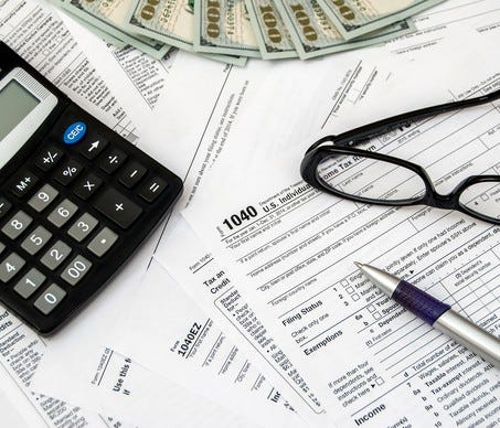 Cluttered surface with calculator, tax forms, $100 bills, pen, and glasses.