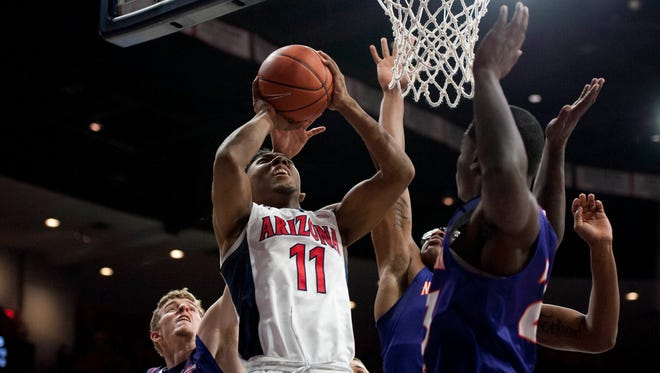 Arizona Wildcats guard Allonzo Trier (11) shoots the ball as Northwestern State Demons forward Matt Killian (13) defends from behind during the first half at McKale Center.
