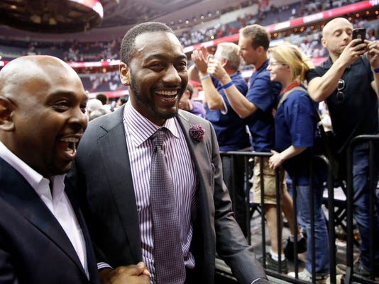 Washington Wizards guard John Wall, right, smiles as he comes off the court after Game 3 of the second round of the NBA basketball playoffs against the Atlanta Hawks, Saturday, May 9, 2015, in Washington. The Wizards won 103-101. (AP Photo/Alex Brandon)