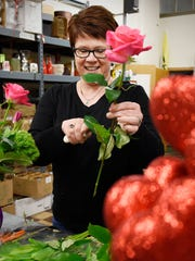 Rhoda Paurus, owner of St. Cloud Floral, trims a rose