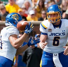 South Dakota State quarterback Austin Sumner, right, bobbles a snap as running back Zach Zenner catches it and runs for a 75-yard touchdown during the first quarter of an NCAA college football game against Missouri Saturday, Aug. 30, 2014, in Columbia, Mo. (AP Photo/L.G. Patterson)