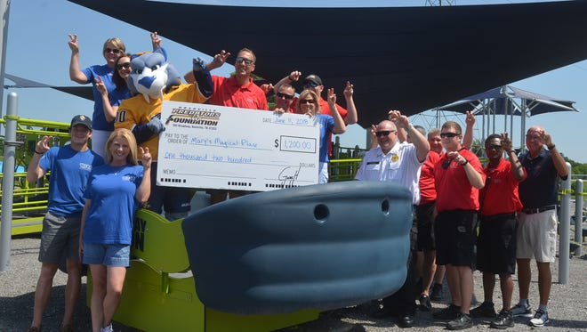 """Members of the Hendersonville Fire Department, Nashville Predators Foundation and Mary's Magical Place do the Predators fan """"fang fingers"""" in celebration of a $1,200 donation to the playground."""