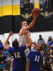 Galena's Moses Wood (11) shoots over Carson's Trenten Robison (12) and Taylor Saarem (11) during their game last season