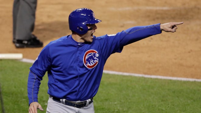 Chicago Cubs' Anthony Rizzo points to Kyle Schwarber after scoring on a hit during the third inning of Game 2 of the Major League Baseball World Series against the Cleveland Indians Wednesday, Oct. 26, 2016, in Cleveland.