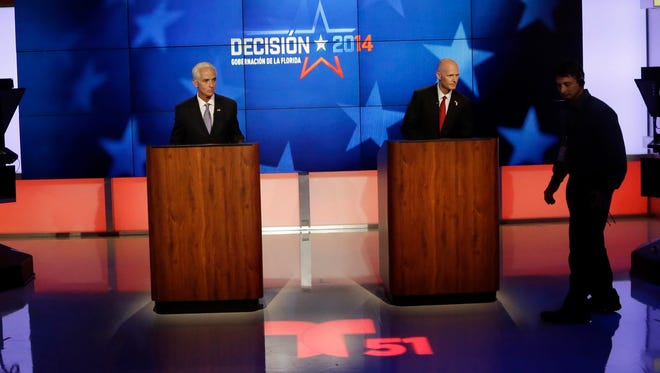 Democrat Charlie Crist, a former Republican governor of Florida, left, and Florida Republican Gov. Rick Scott, right, wait for the start of a gubernatorial debate at the Spanish-language network Telemundo 51, Friday, Oct. 10, in Miramar, Fla.This is the first of three debates before the November election.