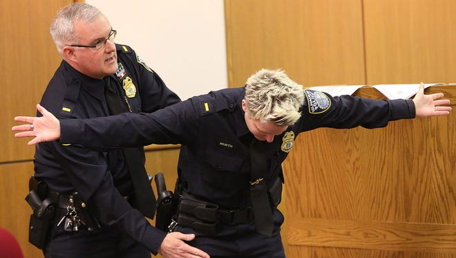 Milwaukee Police Lt. James MacGillis demonstrates standard pat down procedure on a another officer during a 2015 Fire and Police Commission hearing on the firing of a Milwaukee police officer in the shooting death of Dontre Hamilton.