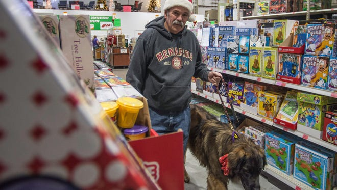 Steven Roberts shops with his dog, Arlo, at Menards for the Toys for Tots program on Tuesday, Dec. 19, 2017.