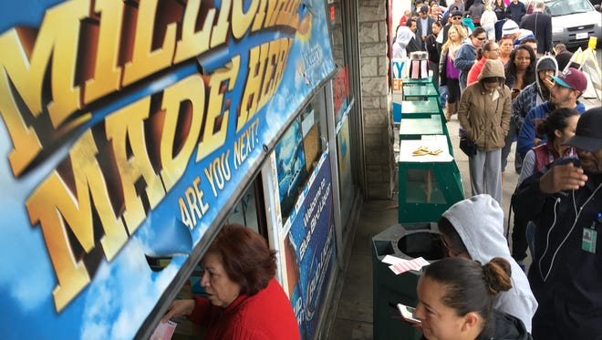 Customers wait in line outside the Blue Bird Liquor store to buy Powerball lottery tickets in Hawthorne, Calif., on Wednesday, Jan. 13, 2016. A lottery official says the estimated Powerball jackpot remains over a billion.