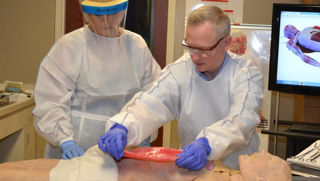 ASUMH student Tammi Lake, left, and ASUMH funeral-science instructor Bradley Sheppard are shown with the SynDaver.