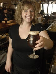 Erika Devine, a bartender at Rock Bottom Restaurant & Brewery, taps a glass of Fallen Angel Abby Ale in this April 2007 file photo.