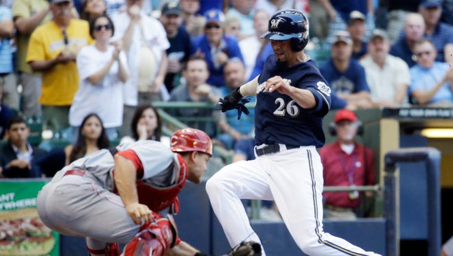 Milwaukee Brewers' Kyle Lohse slides safely past Cincinnati Reds catcher Devin Mesoraco during the fifth inning of a baseball game Wednesday, July 23, 2014, in Milwaukee. Lohse scored from first on a ball hit by Carlos Gomez.