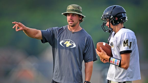Mt. Juliet quarterbacks coach Levi Brown, left, talks with quarterback Alex Landis during practice Wednesday.