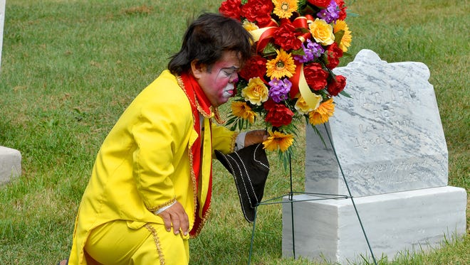 Cole Brothers Circus performer Marvin of Mexico kneels down next to the wreath he just placed next to the headstone of Eva Clark, a young aerialist circus performer killed in 1906. The circus held a small ceremony at Clark's gravesite in Thornrose Cemetery as they remember her in Staunton on Tuesday, Sept. 2, 2014. The circus is currently setup at Augusta Expo where they perform Tuesday to Thursday of this week.