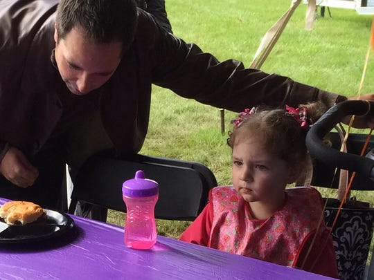 "Nick Vitrano of Ashwaubenon negotiates with daughter Calla, 2 1/2, over ""a couple more bites of that hamburger"" at the Aurora BayCare Medical Center's annual Miracle Baby Celebration on Sunday."