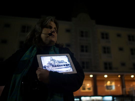 Chesapeake Ghost Walks guide Mindie Burgoyne shows a photo of the Plinhimmon Hotel, now the Plim Plaza, after the hotel burned down in the 1960s. It was the first hotel built by a woman named Rosalie Tilghman Shreve. Some employees of the restaurant believe angels roam the building, randomly bussing tables and placing forgotten food orders.