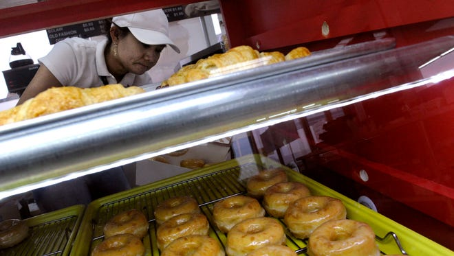 Nicole Pay packs a half-dozen box with pastries at Mustang Donuts Wednesday. The new Abilene shop opened Friday. The original location is in Sweetwater.
