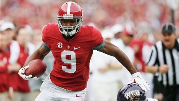 Alabama wide receiver Amari Cooper (9) avoids the tackle