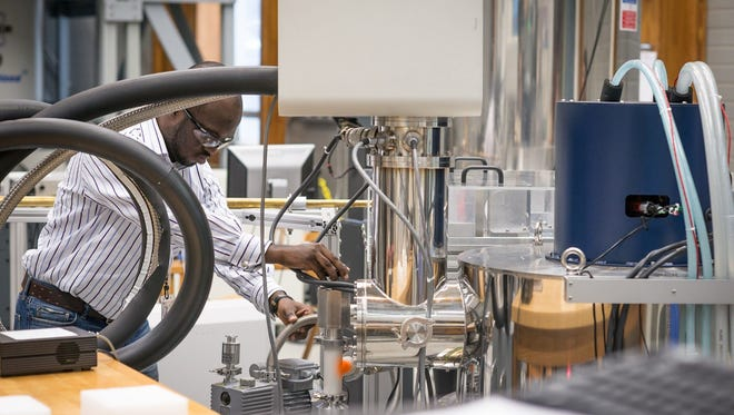 File photo of Mag Lab scientist Adewale Akinfaderin working on an experiment in the lab.