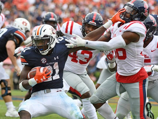 Auburn running back Kerryon Johnson (21) stiff-arms Mississippi defensive back Zedrick Woods (36) during the second half of an NCAA college football game in Auburn, Ala., Saturday, Oct. 7, 2017. Auburn won 44-23. (AP Photo/Thomas Graning)
