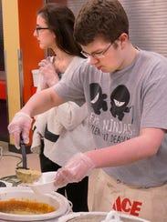 Joshua Pate ladles a bowl of soup. Brianna Doien waits