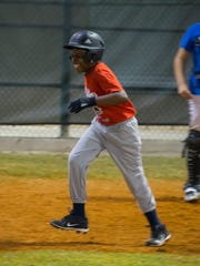 Ka'doffe Mathis, 12, runs to first base after getting a hit during a game at Pelican Baseball Complex in Cape Coral. Mathis, suffered a traumatic brain injury last October.