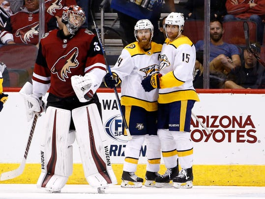 Nashville Predators defenseman Ryan Ellis (4) celebrates his goal against Arizona Coyotes goaltender Darcy Kuemper, left, with right wing Craig Smith (15) during the second period of an NHL hockey game Thursday, March 15, 2018, in Glendale, Ariz. (AP Photo/Ross D. Franklin)