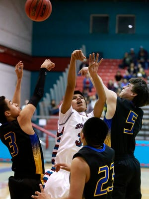 Shiprock's Arvin Begay, center, is contested by Bloomfield's Ty Padilla (3) Malachi Pablo (23) and Damion Sanchez (5) on Thursday at the Chieftain Pit in Shiprock.