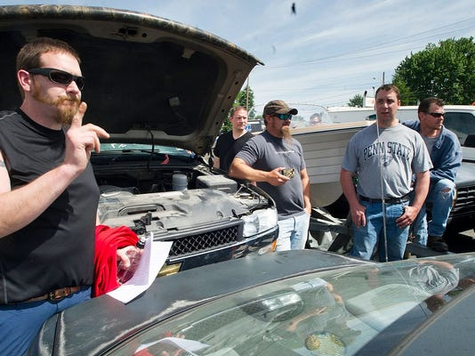 In this 2013 file photo, Pete Lumley, of Willistown, Pa, bids on a Chevy Silverado pickup during the York County Drug Task Force auction.