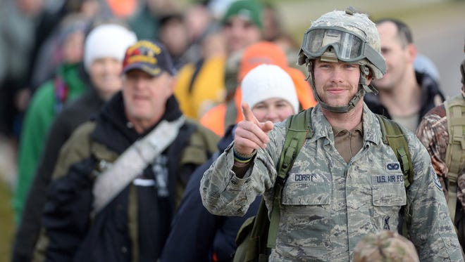 Air Force veteran Kenneth Corry greets a friend along the route as a column of Carry the Fallen marchers head down Holmgren Way in Ashwaubenon taking part in a national ruck march event to reduce veteran suicides November 8, 2014.