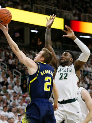 Michigan's Spike Albrecht drives by Michigan State's Branden Dawson for a basket in the first half of their basketball game on Sunday, February 1, 2015 in East Lansing.