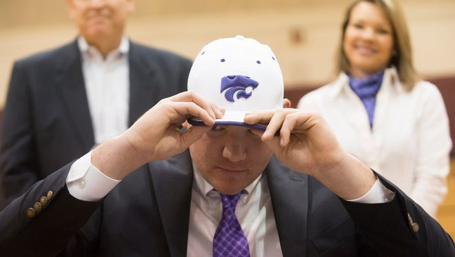 Montgomery Academy football player Tyler Mitchell puts on a Kansas State hat after signing with them on Wednesday February 4, 2015 at Montgomery Academy in Montgomery, Ala.