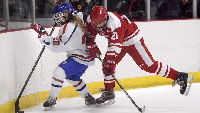 Fairport's Chloe Harvey, left, shields the puck from Penfield's Connor Stuewe during a game at Thomas Creek Ice Arena. The junior defender is one of more than a dozen girls who played on Section V boys hockey teams this winter.