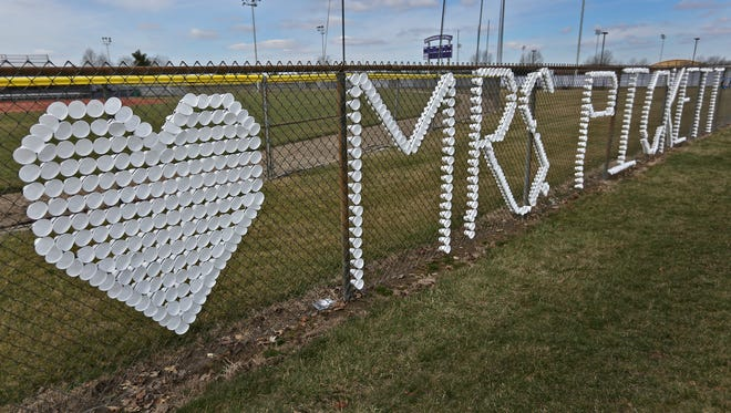 """A sign of support, saying """"We love (a heart symbol) Mrs. Pickett"""" is seen on a fence at White Lick Elementary School before the funeral procession of Boone County Deputy Jacob Pickett passes the school in Brownsburg, Friday, March 9, 2018.  Deputy Pickett's wife, Jennifer Pickett works at the school.  Deputy Pickett was fatally shot the morning of Friday, March 2, while chasing a man fleeing from police."""