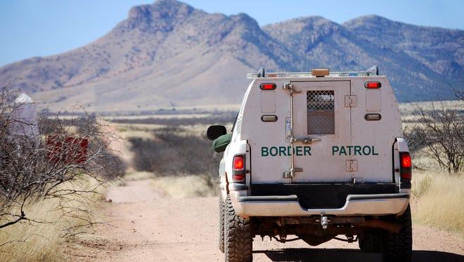 Border patrol agents drive a truck along the U.S.-Mexico border in Arizona.