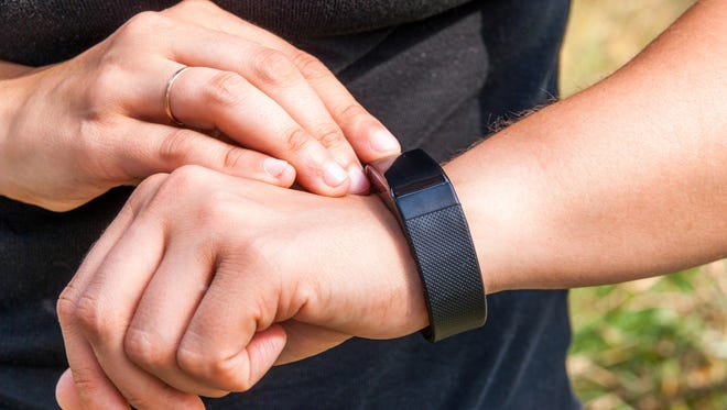 Girl checks the information on the screen of the fitness band. Hands in the picture, close-up