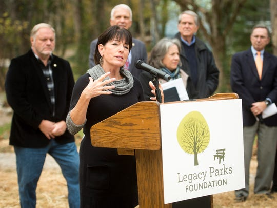 Legacy Parks' executive director Carol Evans, center, speaks at a dedication ceremony for the Baker Creek playground in South Knoxville on Wednesday, Nov. 15, 2017.