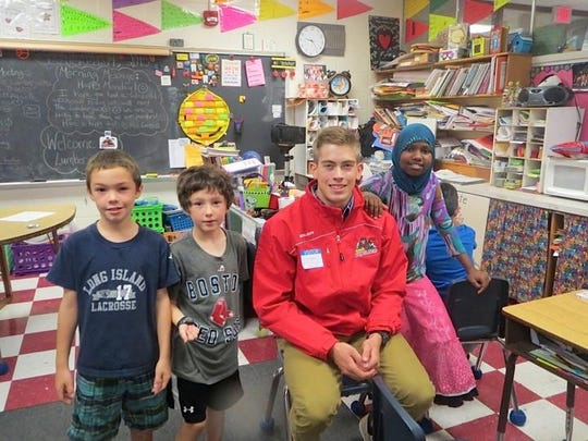 A member of the Vermont Lumberjacks hockey team poses with third-graders at John F. Kennedy Elementary School in Winooski. The Lumberjacks, who are members of the Eastern Hockey League and play their games at Leddy Park in Burlington, visited the class last week. More inside.