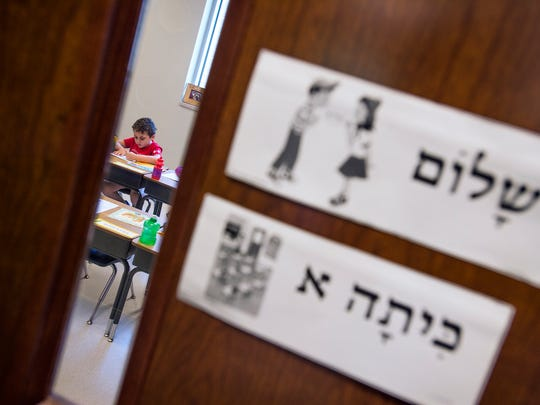 A first-grade student works on the first day of school Wednesday at Temple Israel.