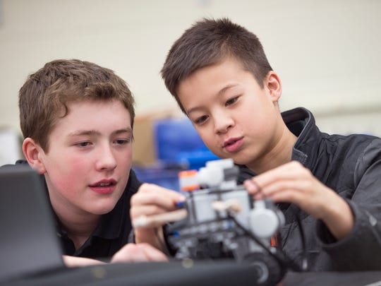 Seton Catholic Central seventh-graders Aiden Howard, left, and Noah Pangilinan work on a robot during a meeting of the robotics club on Jan. 17.