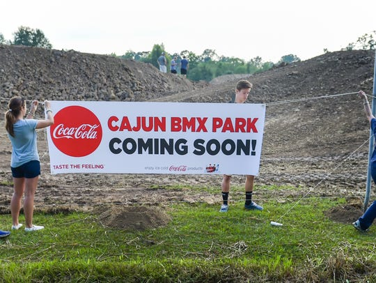Volunteers install sign at Cajun BMX, a 1,200 foot