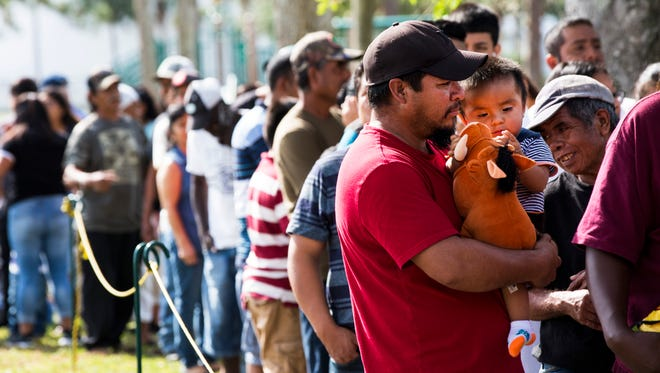 Javier Hernandez, right, waits with his son Javier, 10 months, to receive a Thanksgiving meal donated by St. John the Evangelist Catholic Church and the Guadalupe Center at Airport Park  in Immokalee on Thursday, Nov. 23, 2017.