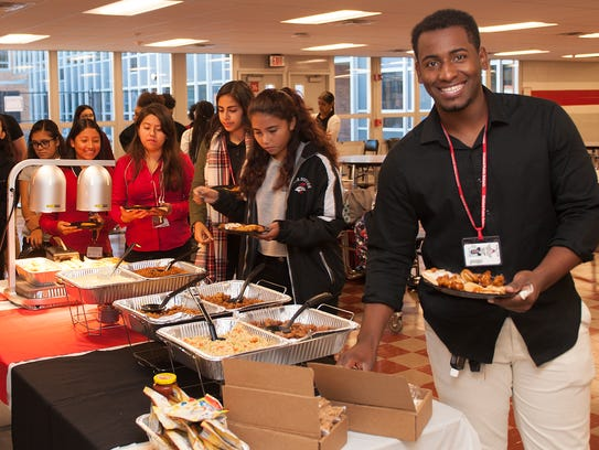 Vineland High School student, José Mateo, right, smiles as he serves himself the on a buffet line at Vineland High School. Sodexo is looking to tweak menu at Vineland High School while getting students to taste the options and make recommendations.