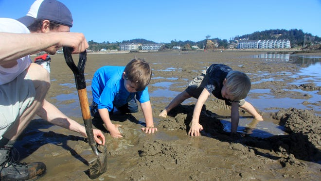 Rylan and Noah Peters search for purple varnish clams in Siletz Bay.