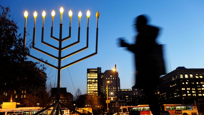A woman passes a large menorah on Independence Mall on the seventh night of Hanukkah last year in Philadelphia.