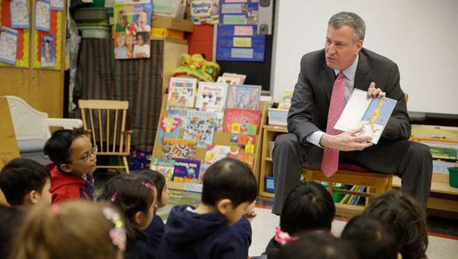 New York City Mayor Bill de Blasio reads to a class of pre-kindergarten students at a public school on Tuesday.