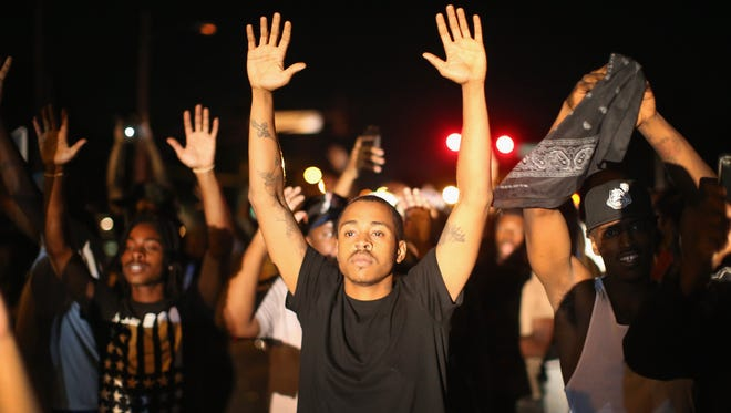 Demonstrators on Aug. 12, 2014, protest the killing of teenager Michael Brown in Ferguson, Missouri. Brown was shot and killed by a police officer on Saturday in the St. Louis suburb of Ferguson.