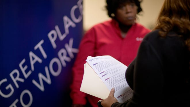 Jimmetta Smith, of Lithonia, Ga., right, the wife of a U.S. Marine veteran, holds her resume while talking with Rhonda Knight, a senior recruiter for Delta Air Lines, at a job fair for veterans and family members at the VFW Post 2681, in Marietta, Ga., in November.