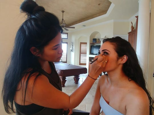 Eri Vincent applyes eyeliner to Hooters Girl Barbara Jay during a photo shoot. Jay hopes she is chosen for the 2019 calendar.