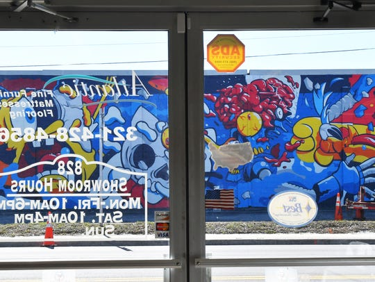 The view of Matt Gondek's mural through the front doors of Atlantic Furniture, Mattresses and Flooring.