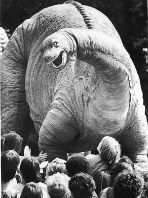A large crowd gathers around a lifelike replica of a Brontosaurus (now called Apatosaurus) in Boston in 1984.